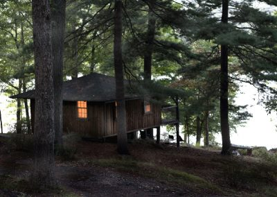 A rustic camp by the water at twilight, with a single window lit.
