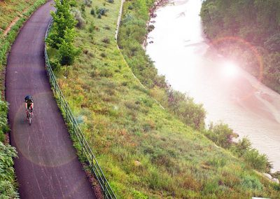 A solitary cyclist on a bike path between a field and a river in the early morning.